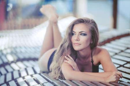 Portrait of woman sunbathing in bikini at tropical travel resort  Beautiful young woman lying on sun lounger  Summer  Outdoor