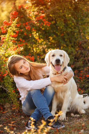 portrait of Smiling young girl posing with a labrador retriever dog out in autumn beautiful park Stock Photo