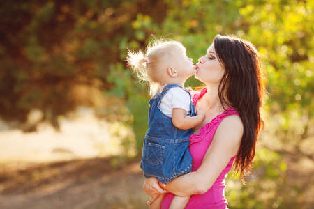 caucasoid race: Young mother with child outside on a summer day