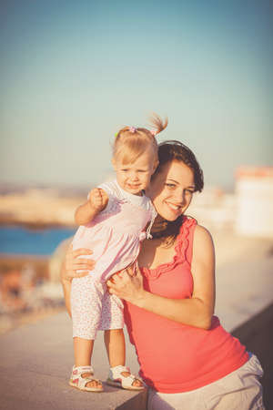 belonging to the caucasoid race: Young mother with child outside on a summer day