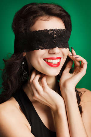 portrait of sexy and beautiful woman with a black lace on her eyes and a black boa on her shoulders photo