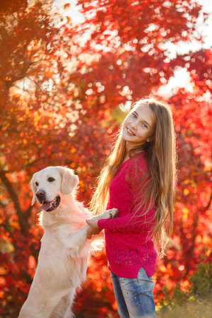portrait of Smiling young girl posing with a labrador retriever dog out in autumn beautiful park photo