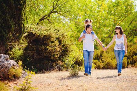 outdoor: Joven familia feliz con el niño en reposo al aire libre en el parque de verano