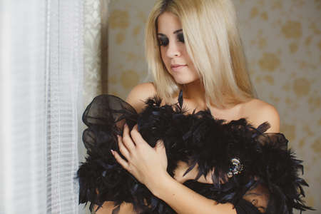 Portrait of young beautiful blonde woman wearing boa on her shoulders photo