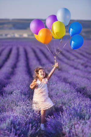 Smiling girl picking flowers in lilac lavender field photo