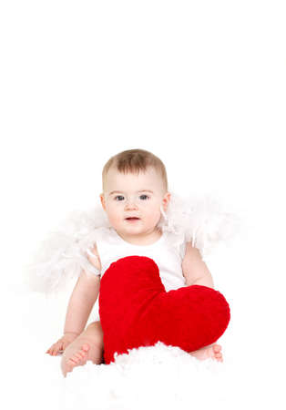portrait of a Cute adorable little valentine angel with red soft heart isolated on white background photo
