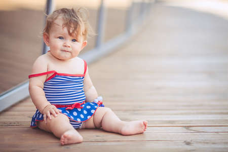 portrait of a little adorable infant girl sitting on the floor in summer park outdoors photo