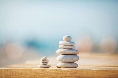 piedras zen: zen piedras jy banch de madera en la playa cerca del mar al aire libre