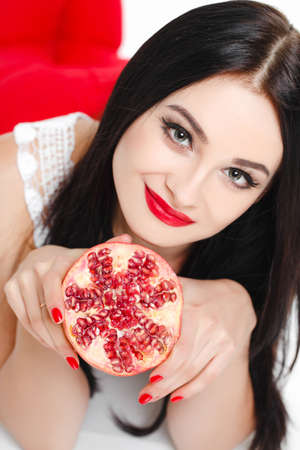 entice: Portrait of young beautiful woman with bright makeup and red lips holding pomegranate in her hands, isolated on white background
