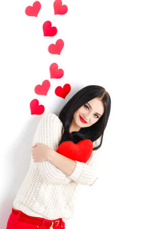pretty s shiny: Valentine s Day  Portrait of Beautiful smiling brunette woman with heart in her hands and behind isolated on white background