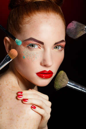 Beautiful woman with Makeup Brushes  Bright Holiday Make-up for Brunette Woman with Brown Eyes  Orange and Yellow Make up  Beautiful Face  Makeover  Perfect Skin  Applying Makeup photo