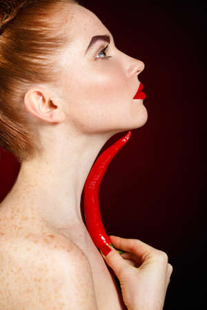 portrait of beautiful redhair fashionionable woman with spicy hot red cayenne chili pepper photo