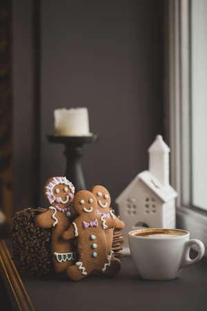 Smiling gingerbread man standing next to a Cup of coffee at the window, close with shallow DOF copy space for text in Internet