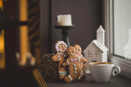 Smiling gingerbread man standing next to a Cup of coffee at the window, close with shallow DOF copy space for text in Internet photo
