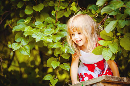 Portrait of beautiful little girl in summer green park photo