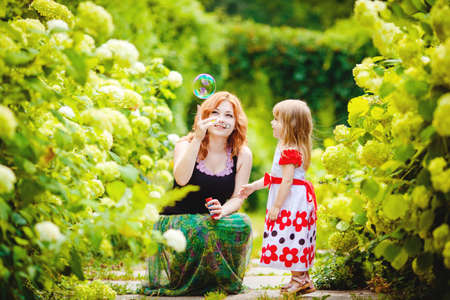holiday home: Mother and daughter playing in green summer park outdoors
