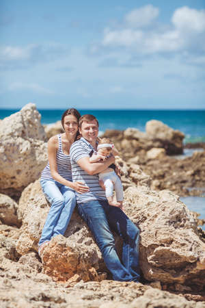 portrait of family of three having fun together by the ocean shore and enjoying the view  Outdoors photo