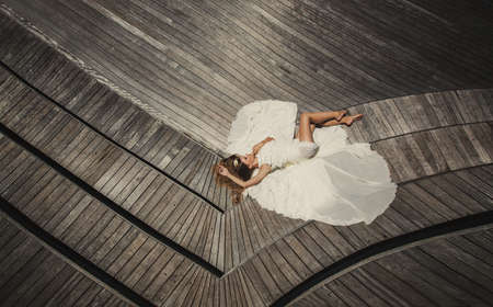 belonging to the caucasoid race: portrait of beautiful model bride in white wedding dress lying relaxing on tropical vacation