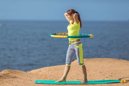 woman rotates hula hoop on summer beach photo