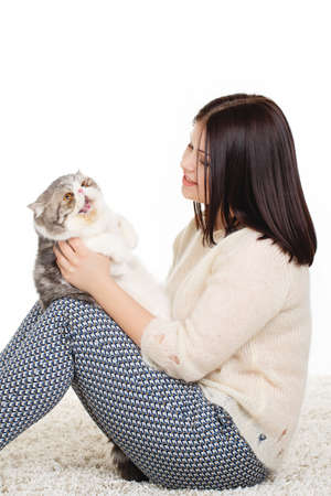 elegant woman wearing grey felt hat in retro style holding cat  Glance of woman and cat is the same  Resembling, similarity  photo