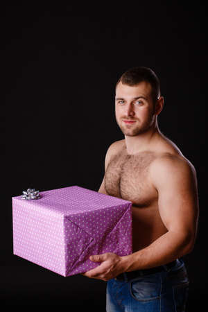 Image of muscular man holding xmas gifts, isolated on black photo