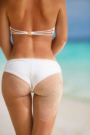 Sexy sandy woman buttocks on tropical beach background near ocean photo