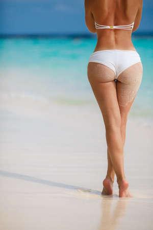 Sexy Frau Gesäß auf sandigen tropischen Strand Hintergrund in der Nähe von Meer