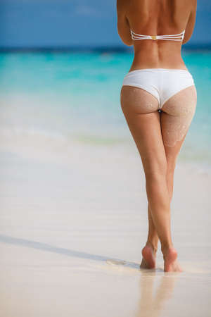 Sexy sandy woman buttocks on tropical beach background near ocean Stock Photo