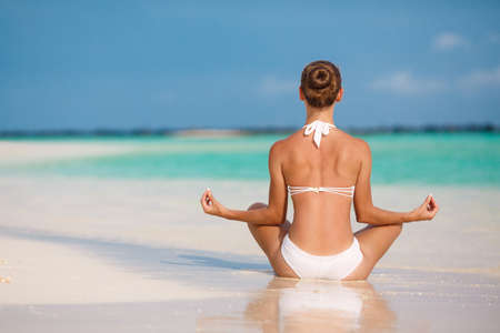 portrait of young woman doing yoga exercises on tropical maldivian beach near ocean photo