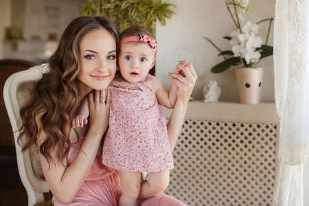 Mother with little baby in home interior young beautiful mom hugging daughter, pretty brunet woman playing with cute small girl, smiling girl holding adorable sweet child, happy family concept photo