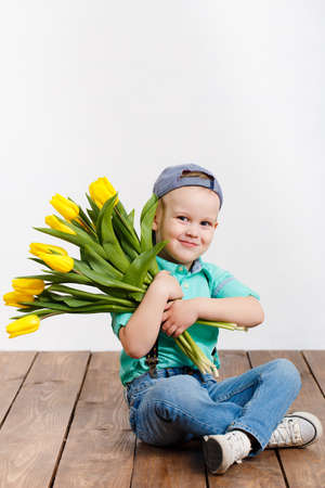 Smiling boy holding a bouquet of yellow tulips in hands sitting on wooden floor photo