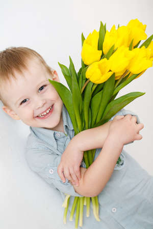 portrait of Smiling boy with a bouquet of yellow tulips flowers in hands standing near white wall photo