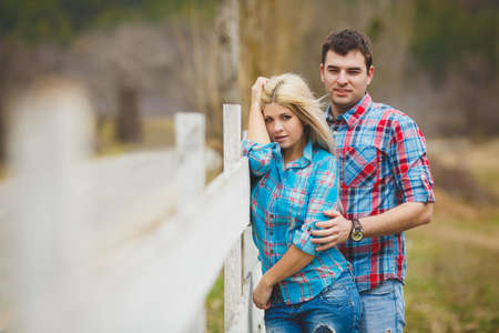 Portrait of happy young couple wearing shirts having fun outdoors near fence in park photo