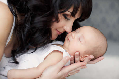 new born baby boy: portrait of Young happy mother with her newborn baby lying on bed in home interior