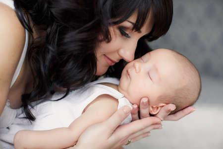 nato: Ritratto di giovane madre felice con il suo neonato sdraiato sul letto in home interior Archivio Fotografico