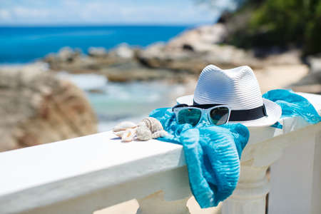 Hat and sunglasses lying on white railing on ocean beach background photo