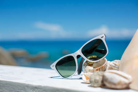 Sunglasses and beautiful seashells lying on a background of blue ocean