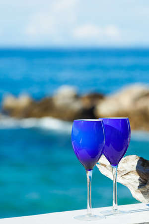 Two Glasses of Wine Standing on Old Table at the Beach on the Pacific Coast photo