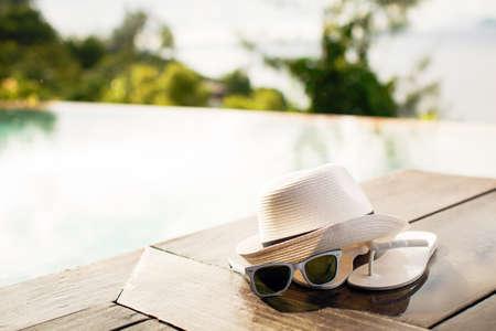 Ein Paar weiße Flip-Flops am Pool auf einem hellen blau, grün, violett und weiß gestreiften Handtuch mit Sonnenbrille und großen weißen Schlapphut Lizenzfreie Bilder