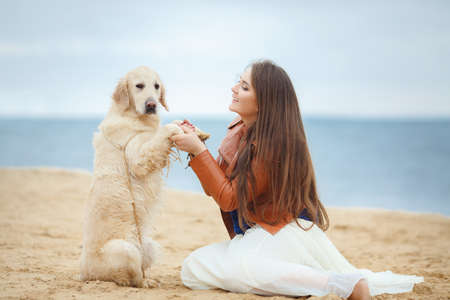 endear: portrait of Beautiful woman with her dog on the beach near sea