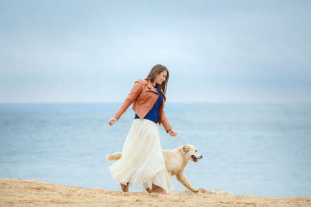 portrait of beautiful woman with her dog retriever playing on the beach by the sea photo