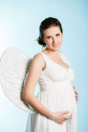 Portrait of a beautiful angelic pregnant woman  Angel photo