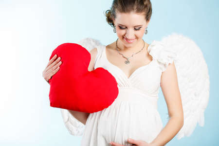 Portrait of a beautiful angelic pregnant woman  Angel with red heart in her hands photo