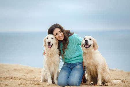 Porträt einer schönen Frau sitzt am Ufer des Meeres mit einem verspielten jungen Hund, Natur