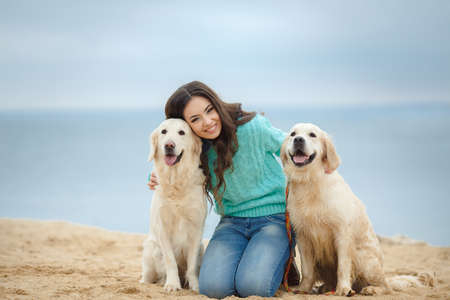Portrait of a beautiful woman sitting on the sea shore with a playful young dog, Nature photo