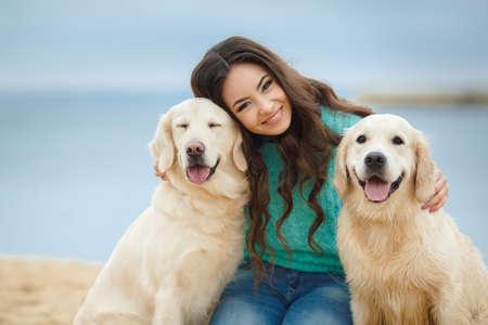 Portret van een mooie vrouw zittend op de kust met een speelse jonge hond, Natuur