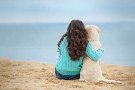 Beautiful woman with her dog playing on the sea shore  Reklamní fotografie