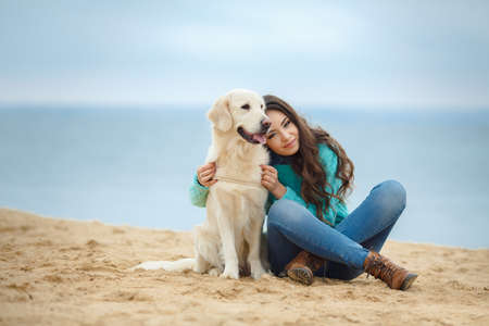 Portrait of a beautiful woman sitting on the sea shore with a playful young dog, Nature Stock Photo