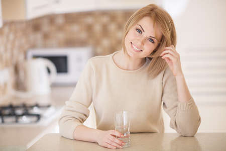 Charming woman holding glass filled with water while standing looking into the camera in the kitchen photo
