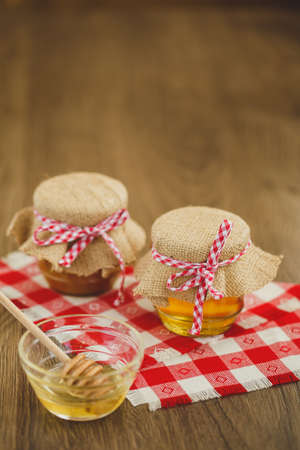 two jars of honey,honeycombs and wooden drizzler on table on yellow background photo